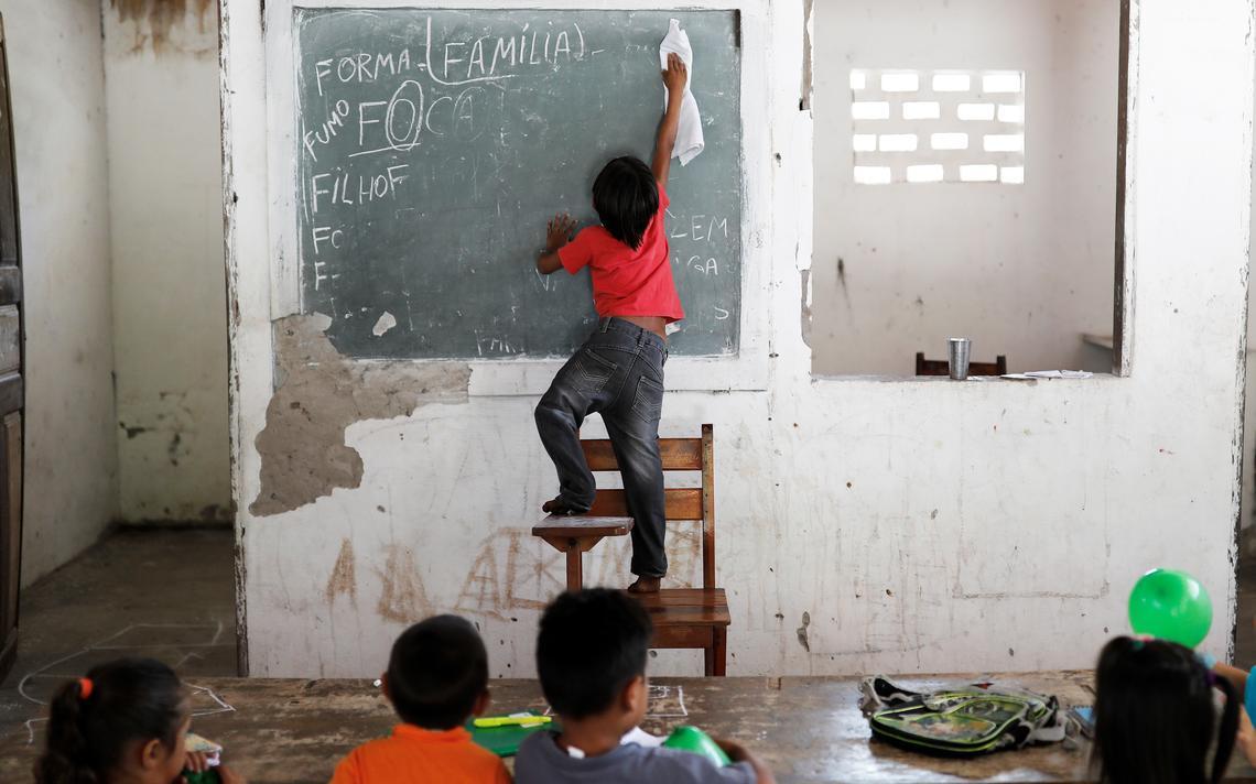 Estudante apaga a lousa em uma escola no Morro do Veridiano, na cidade de Belágua, no Maranhão