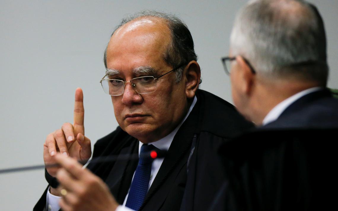 Sentado em mesa do tribunal, Gilmar Mendes ergue o dedo indicador direito, com braço direito apoiado sobre a mesa. Ele está com semblante sério. Ao seu lado, Edson Fachin observa Gilmar.