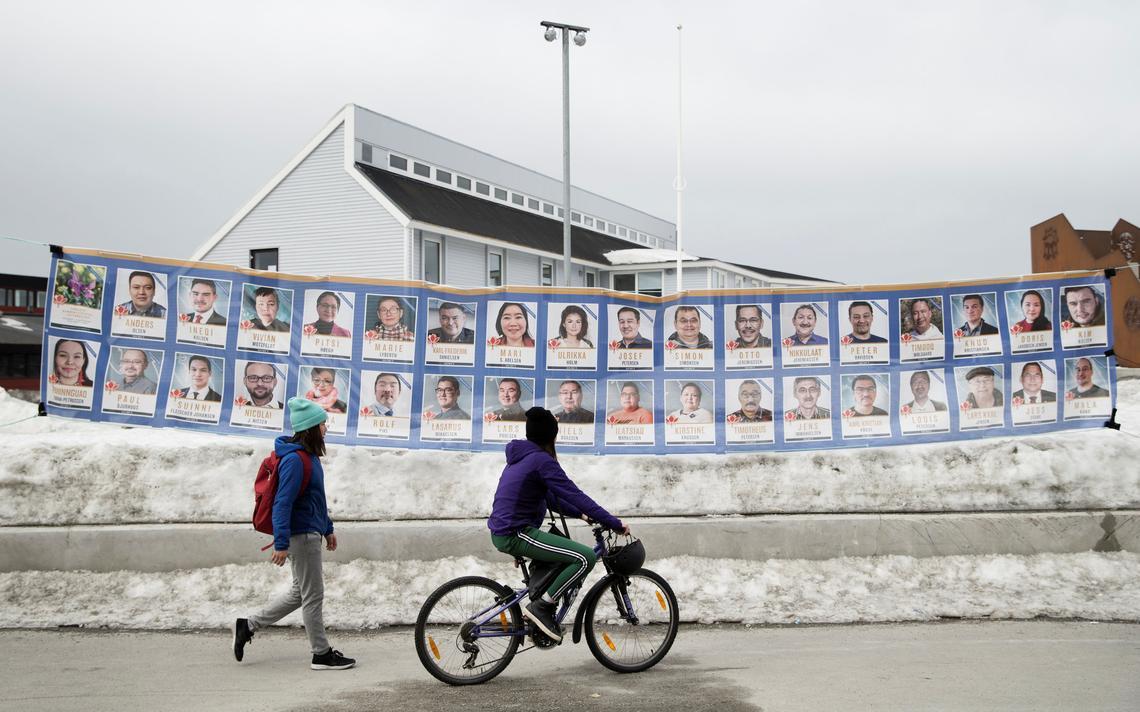 Duas garotas, uma a pé e uma de bicicleta, passam em frente a um mural com pôsteres de candidatos. Existe gelo na rua.