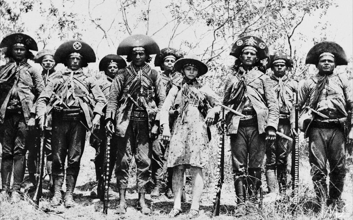 10 cangaceiros posam para foto. Todos estão em pé, com suas vestes, armas apoiadas no chão. Estão no meio da mata.