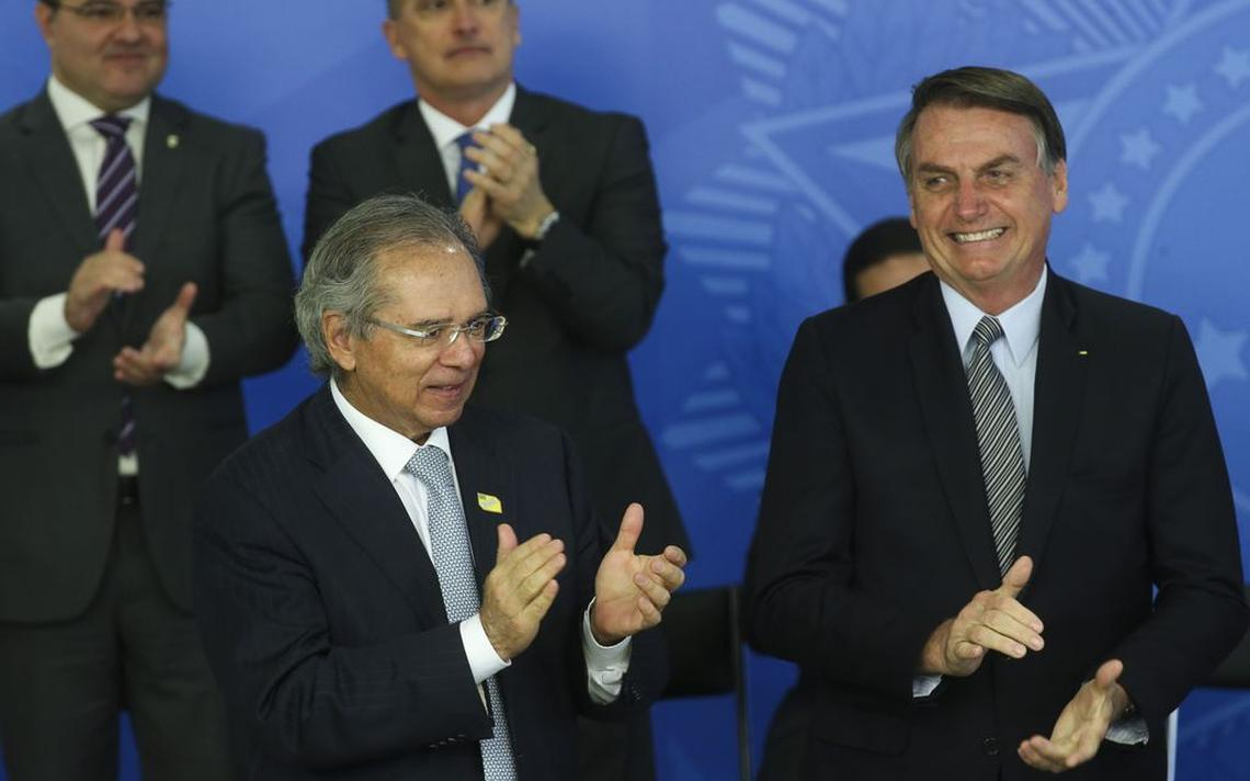 O presidente Jair Bolsonaro (dir.) e o ministro da Economia, Paulo Guedes, em evento em Brasília em outubro de 2019. Os dois batem palmas e sorriem no primeiro plano. Ao fundo, desfocado, o ministro-chefe da Casa Civil, Onyx Lorenzoni, também bate palmas.