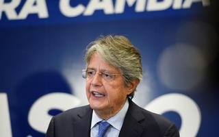 Guillermo Lasso discursa diante de painel azul com mensagens de sua campanha eleitoral à presidência do Equador