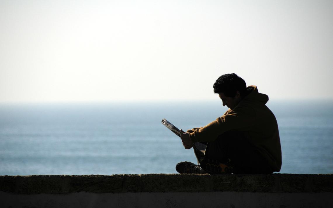 Homem lê livro sozinho próximo ao mar