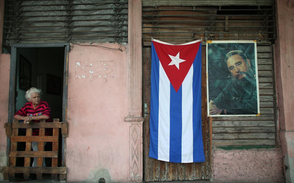 Bandeira de Cuba ao lado de retrato de Fidel