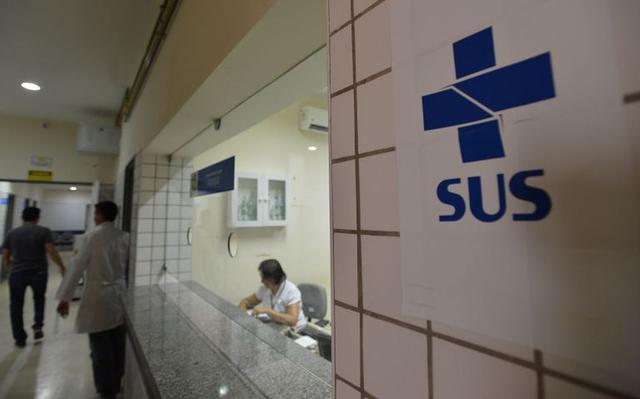 Foto mostra placa com logo do SUS ao lado de guichê de atendimento em hospital público