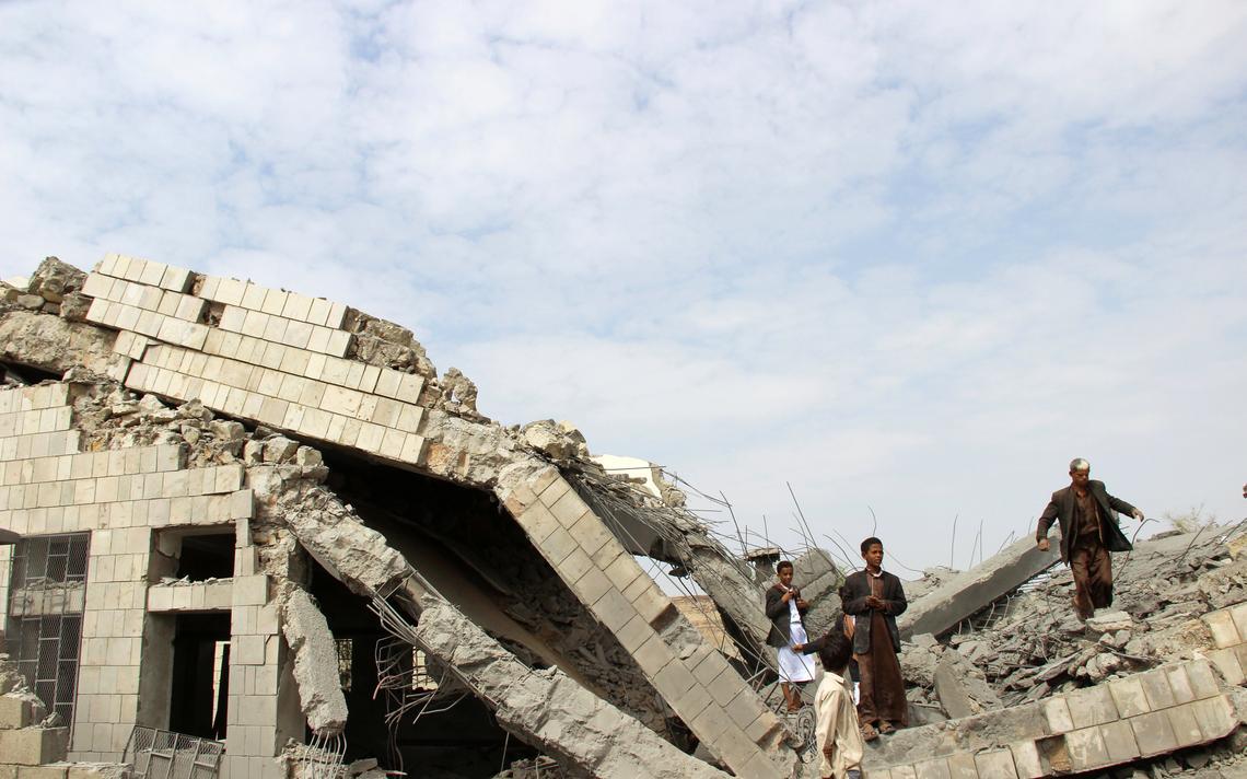 Escola destruída, com ferro e concreto à mostra. Quatro pessoas estão em cima dos destroços.