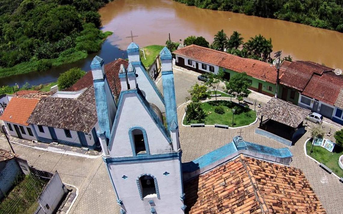 Igreja vista de cima, com ruas de paralelepípedo em volta. Ao funfo, um rio com uma mata densa e um monte com vegetação densa.