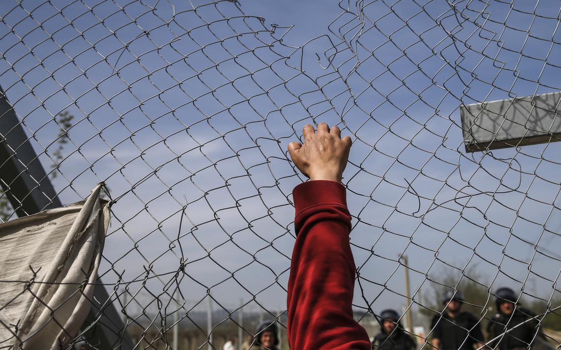 Mão de imigrante puxa cerca na fronteira. Em frente, guardas observam.
