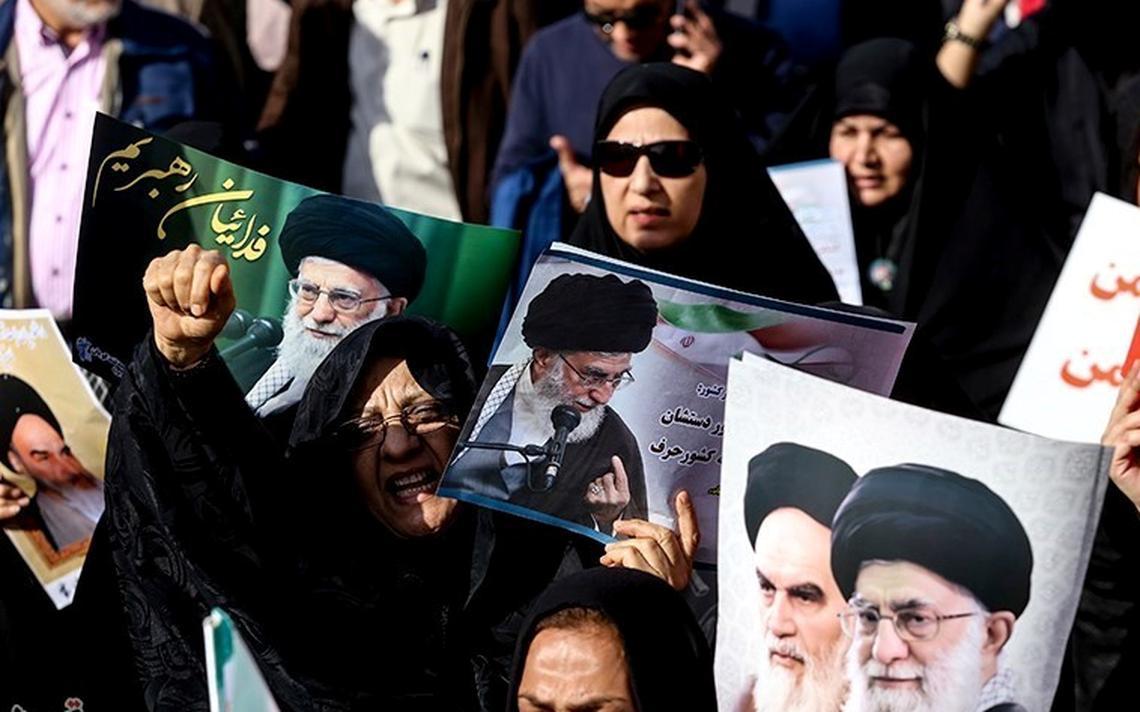 Manifestantes, sobretudo mulheres usando véu, com fotos do aiatolá Ali Khamenei e do aiatolá Ruhollah Khomeini.