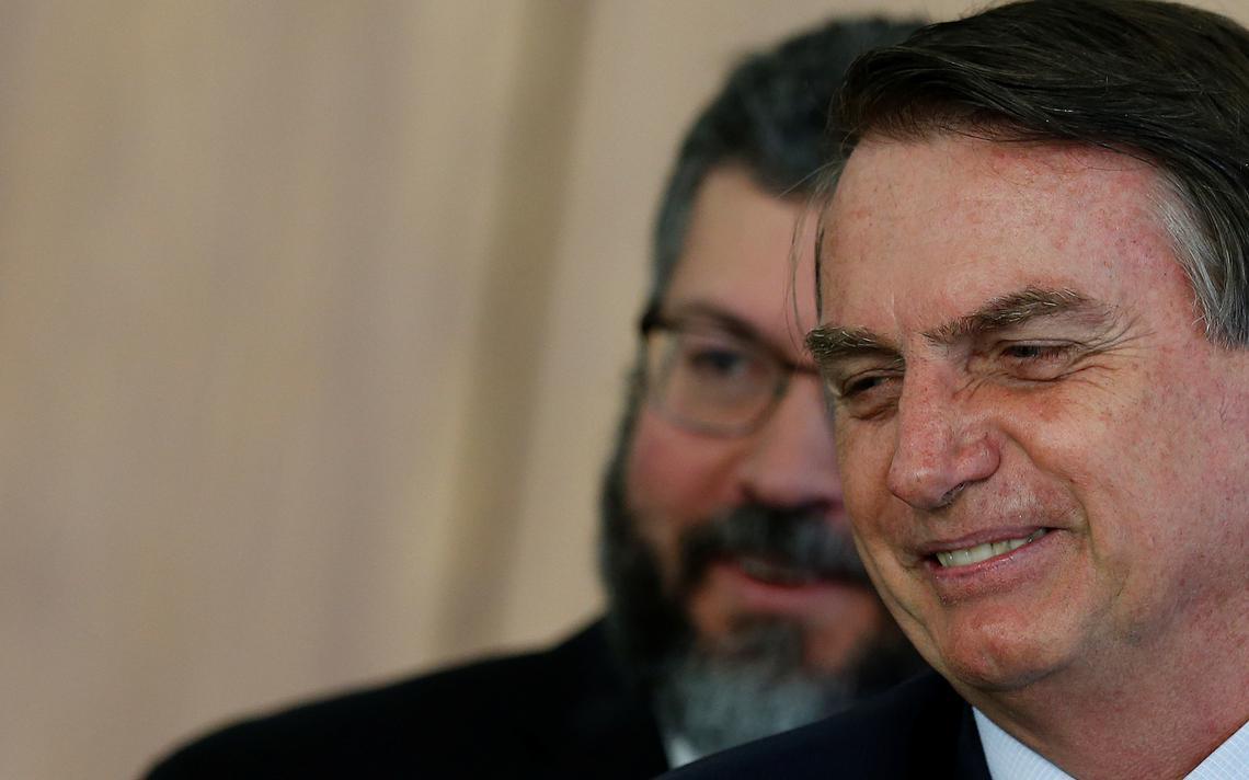 O presidente Jair Bolsonaro à frente de seu chanceler, Ernesto Araújo