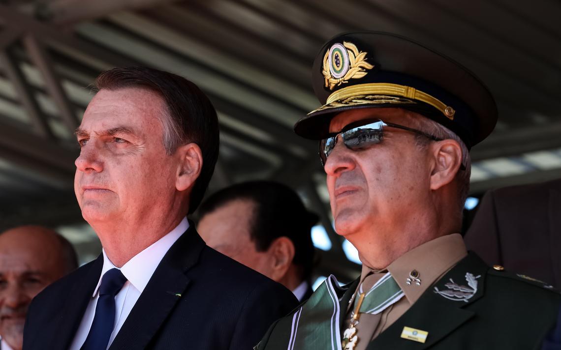 Fardado, general Ramos está ao lado de Bolsonaro. Os dois estão em pé, embaixo de um toldo e observam solenidade.