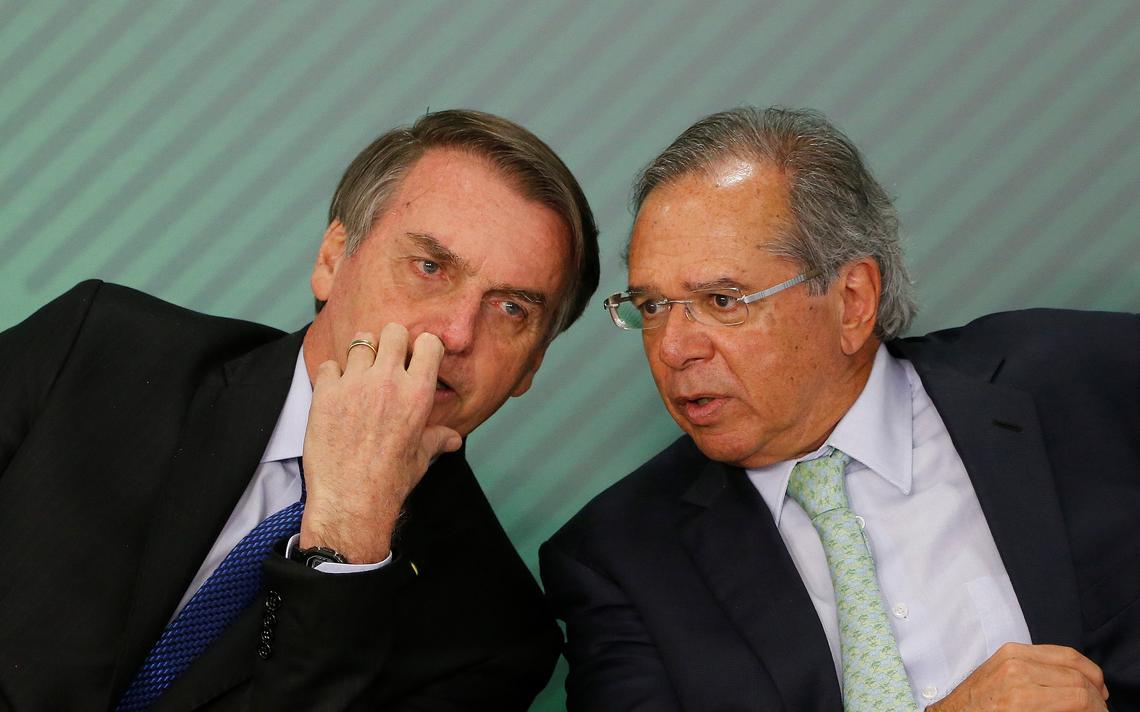 Sentados lado a lado, Bolsonaro e Guedes conversam durante evento, inclinados um na direção do outro.