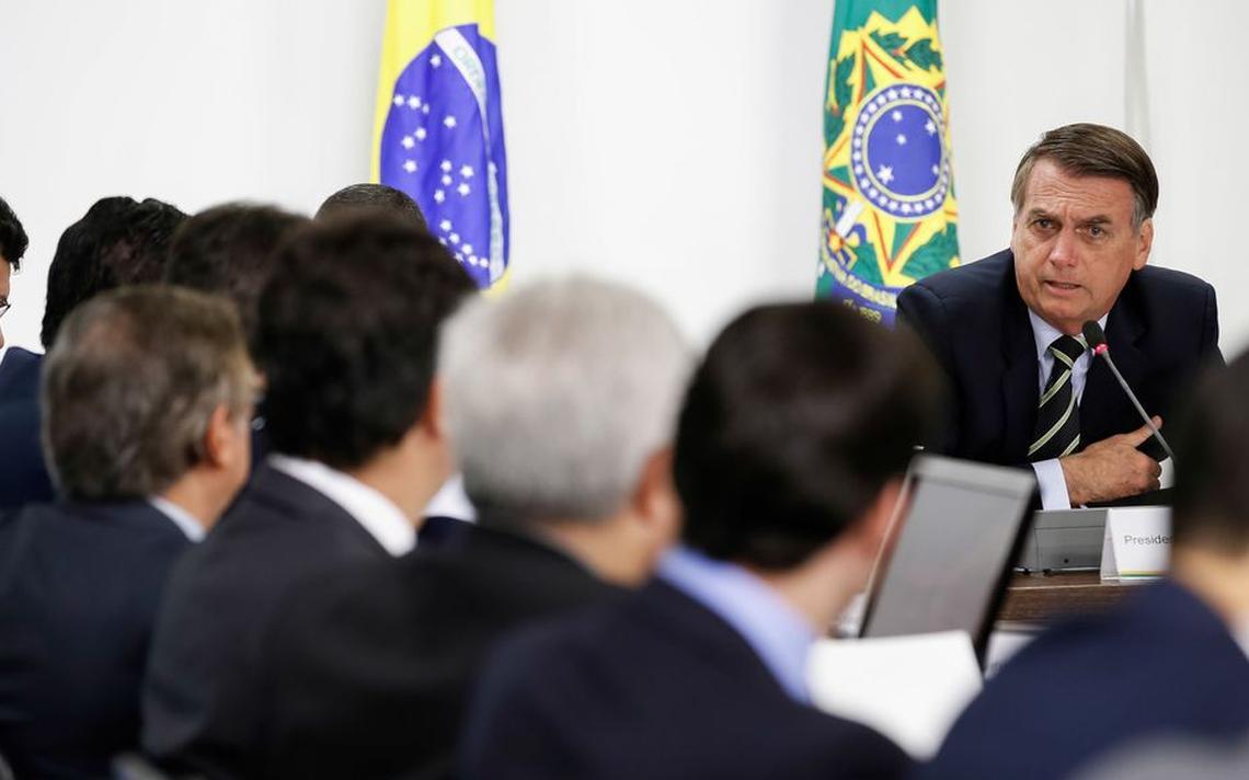 Sentado à mesa de reunião, Bolsonaro fala e olha em direção a seus ministros. Eles observam o presidente.