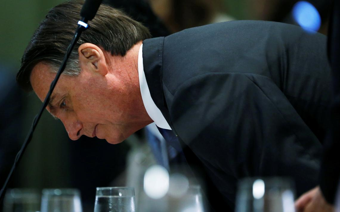 Bolsonaro se sentando. À frente dele, uma mesa com taças d'água enfileiradas.