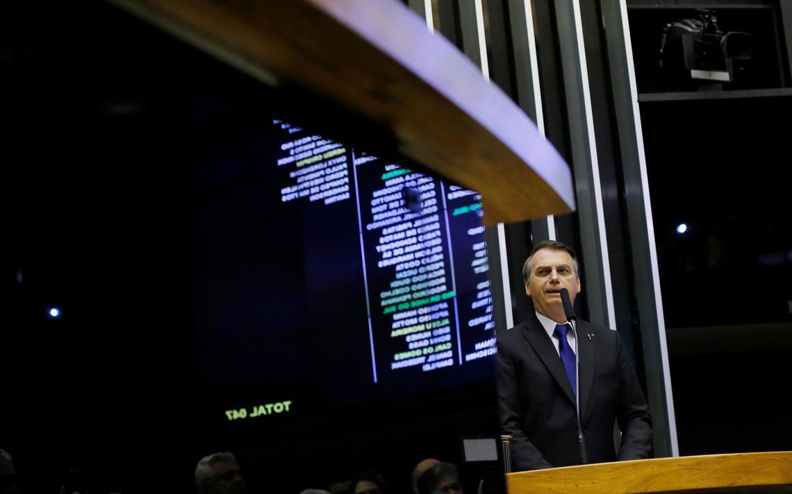Bolsonaro está no púlpito da Câmara. Em pé, ele fala ao microfone. Atrás dele, o painel com o nome dos deputados presentes.