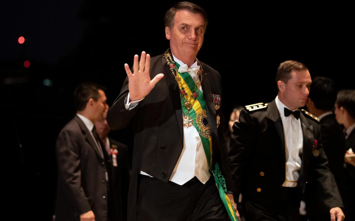 O presidente Bolsonaro acenando, usando a faixa presidencial