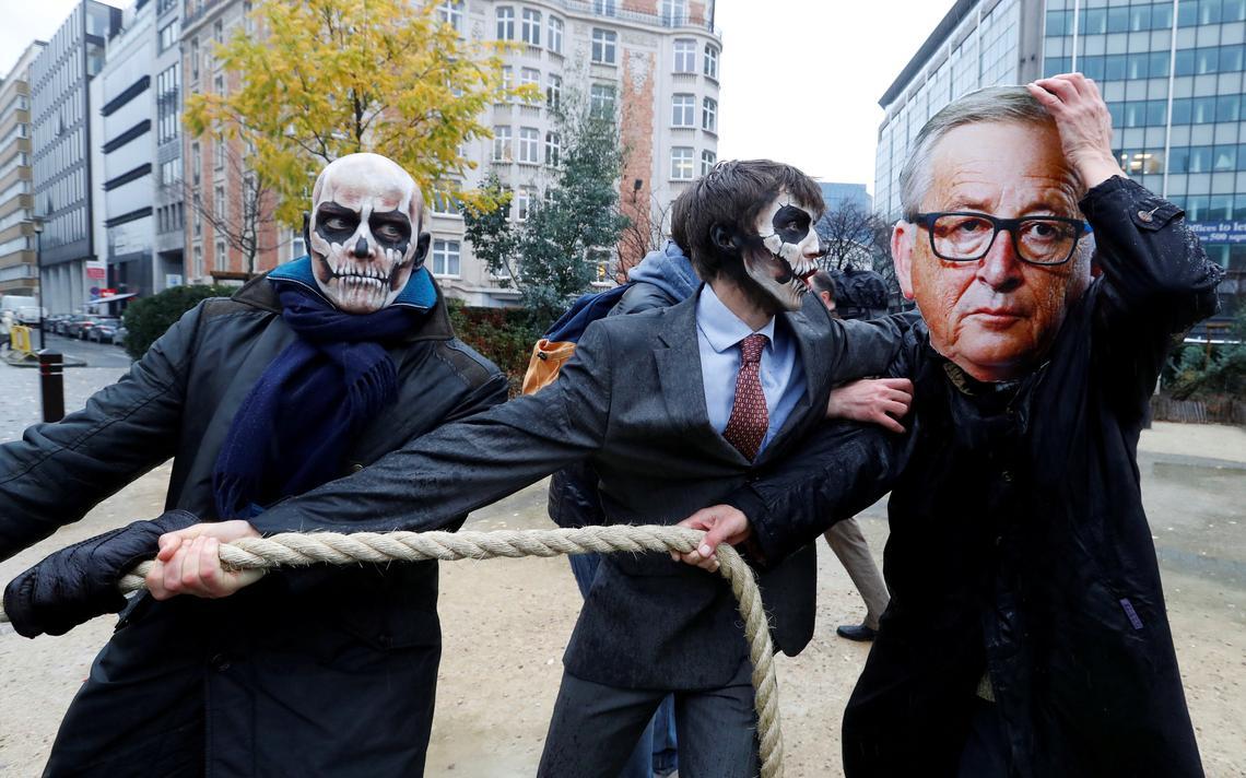 Homem mascarado como presidente da Comissão Europeia Jean-Claude Juncker protesta contra glifosato em Bruxelas em novembro de 2017