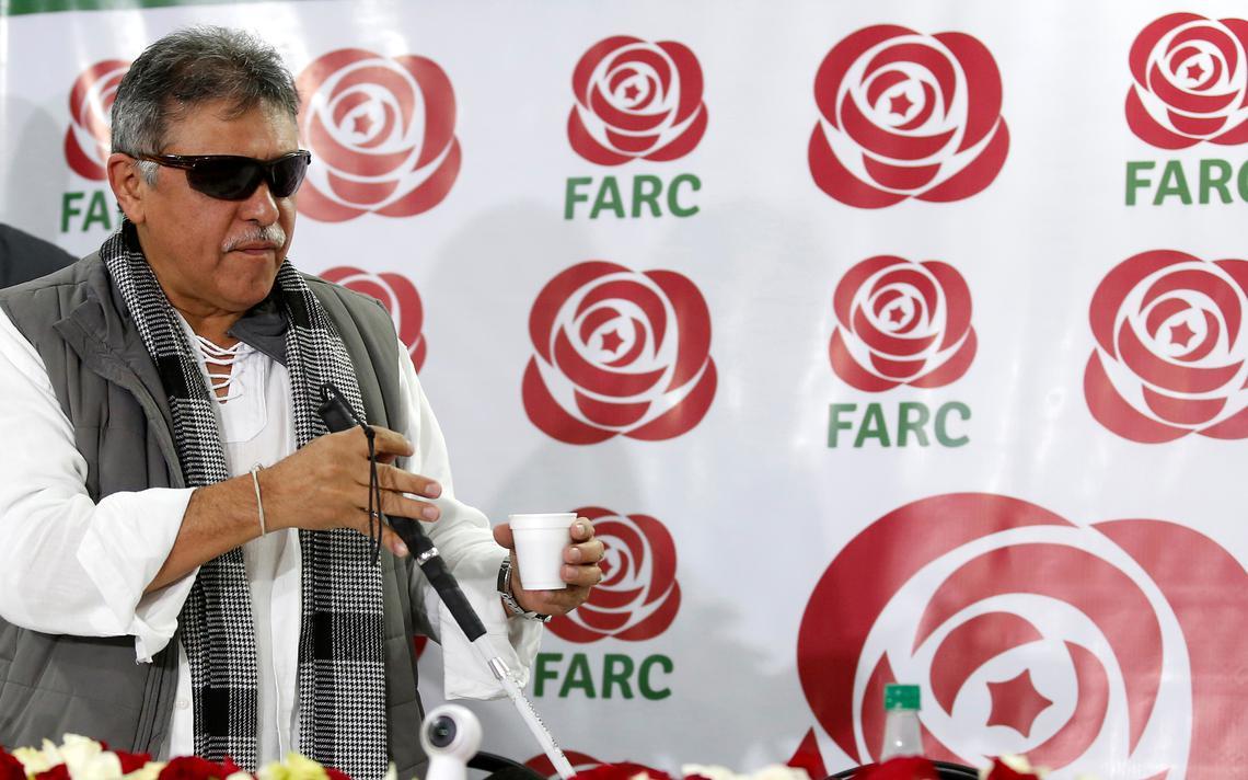 Em pé em frente à mesa de entrevista, Santrich segura um copo com café. Ele está usando óculos escuros. Atrás, um painel com o nome e o símbolo do partido político Far, que é uma rosa vermelha.
