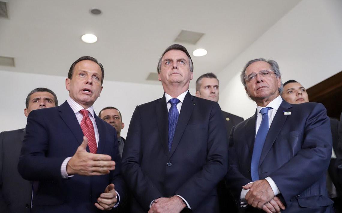 Em pé dentro de uma sala do palácio do governo, Doria fala e gesticula. Bolsonaro e Paulo Guedes estão ao lado do governador.