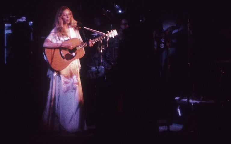 Cantora Joni Mitchell, conhecida por usar várias afinações de violão, em show de 1974, em Los Angeles