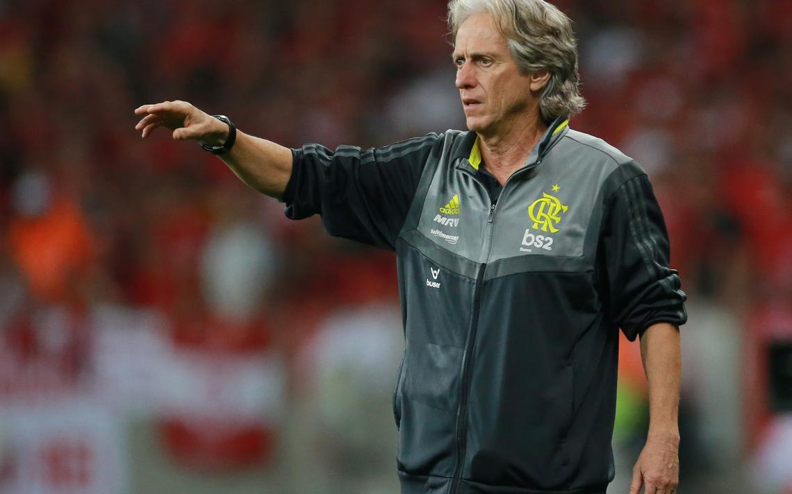 O treinador Jorge Jesus comanda o Flamengo em jogo contra o Internacional, pela Libertadores. Ele veste um casaco cinza com o símbolo do Flamengo e aponta para o campo, orientando os jogadores