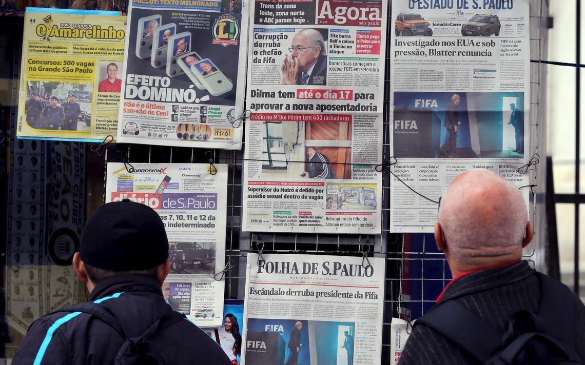Homens observam jornais numa banca