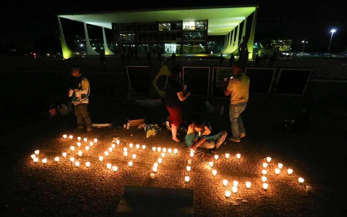 Quatro manifestantes com bandeiras e camisas do Brasil., em frente ao prédio do Supremo. Está de noite e eles colocaram velas no chão que formam a palavra