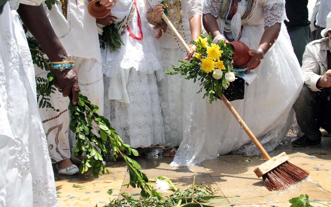 Com vassoura, água e ramos de folhas, baianas lavam a parte externa da Igreja do Bonfim
