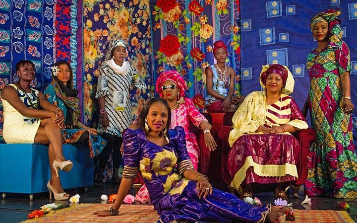 Oito das artistas do grupo posam para foto, com fundo colorido e estampas de flores. Elas usam vestes de diferentes cores.
