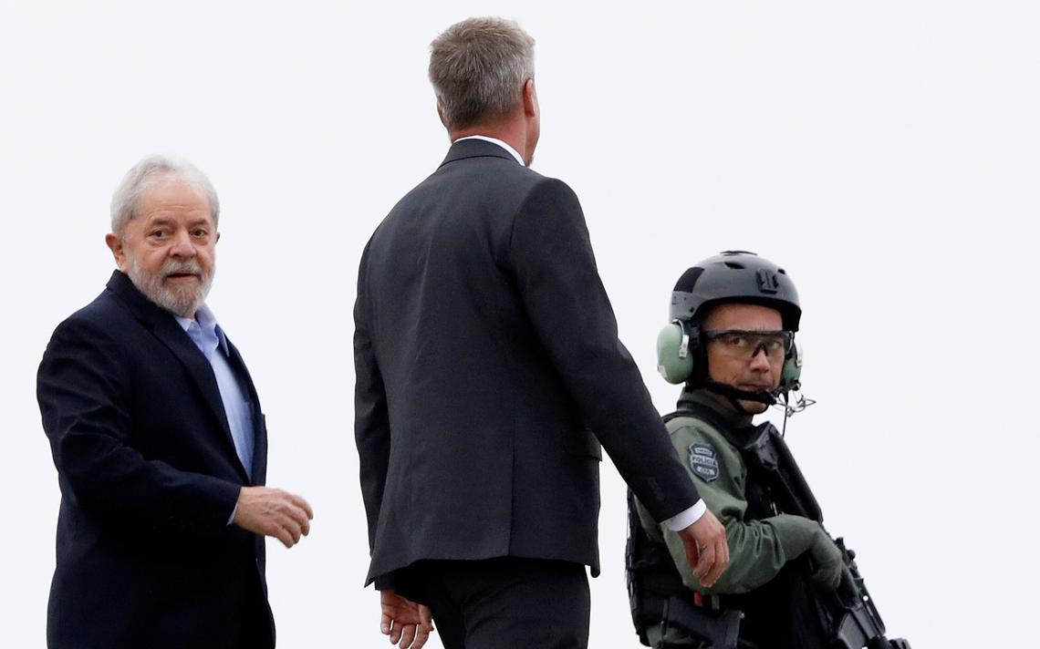 Em heliponto, Lula ao lado de um homem e um policial armado