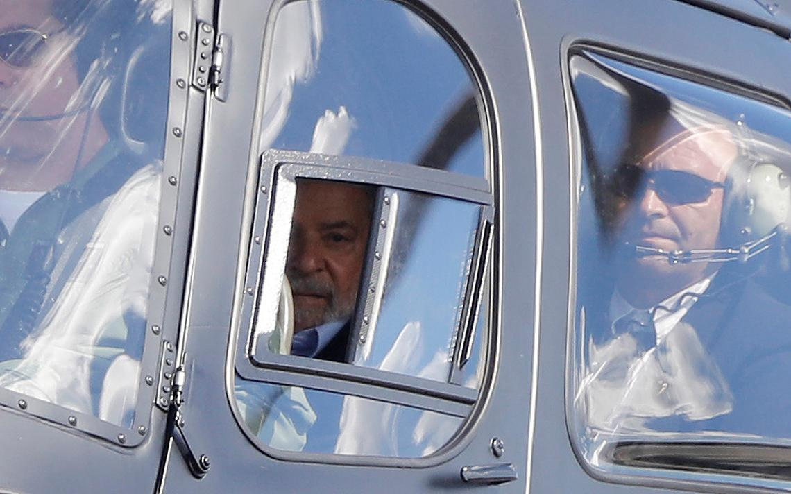Lula dentro de um helicóptero, escoltado por policiais.