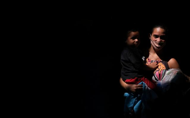 Mulher vestindo máscara carrega filho no colo e sacola com alimentos no outro braço
