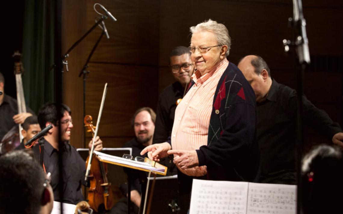 Maestro e professor Olivier Toni rodeado de músicos durante um ensaio