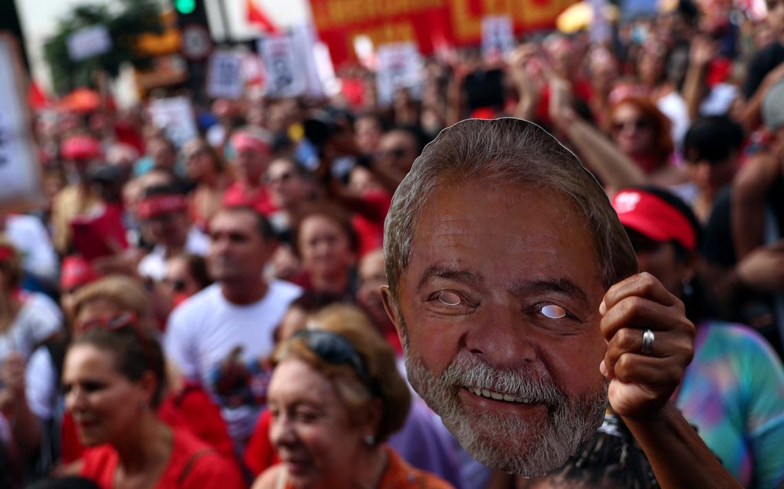 Ato na rua de apoiadores de Lula. Uma manifestante segura no alto uma máscara que representa o rosto de Lula.