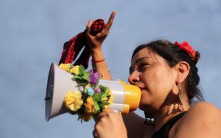 Mulher em manifestação de rua levanta a mão no ar e fala em um alto-falante decorado com flores