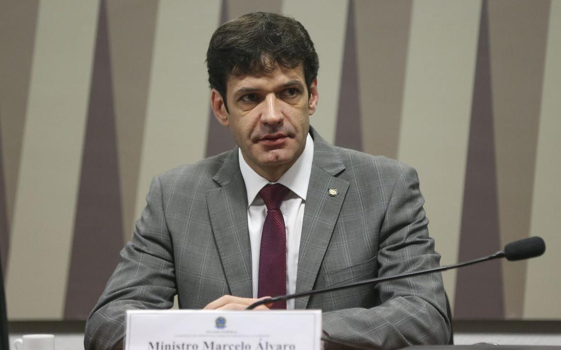 Álvaro Antônio sentado à mesa, com microfone à frente. À frente dele, uma placa com seu nome e cargo.
