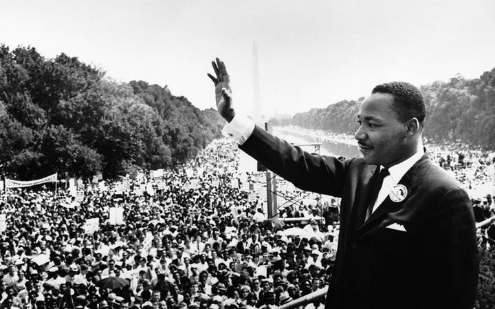 Em cima de um palco, Luther King acena para milhares de manifestantes. Ao fundo, o monumento do obelisco de Washington.