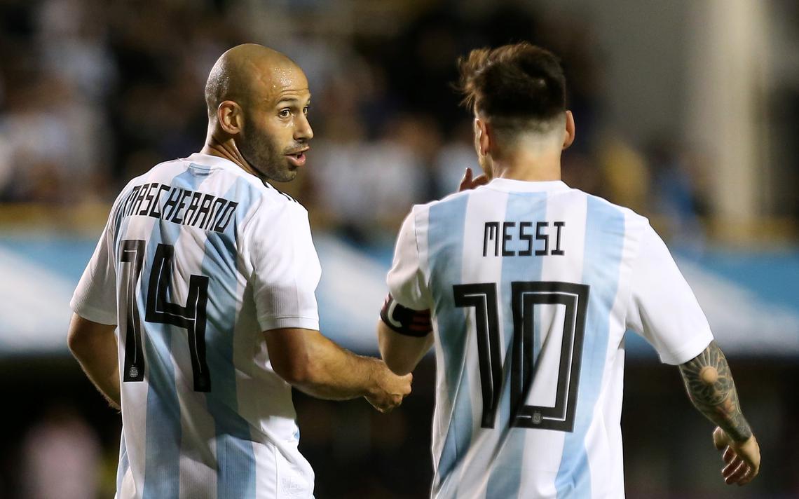 Lado a lado, os dois jogadores conversam dentro de campo. Messi está de costas. Só o rosto de Mascherano aparece na foto.