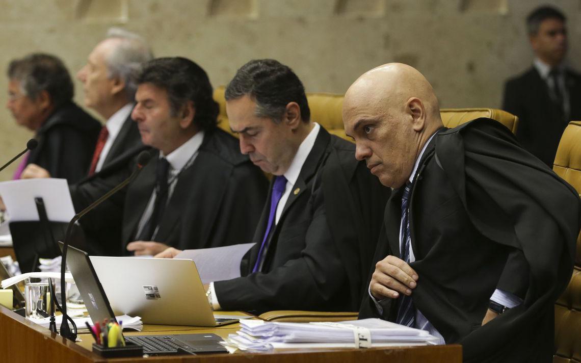 Lado a lado sentados à mesa no plenário, ministros do Supremo observam a sessão, consultando pastas e computadores que estão sobre a mesa.