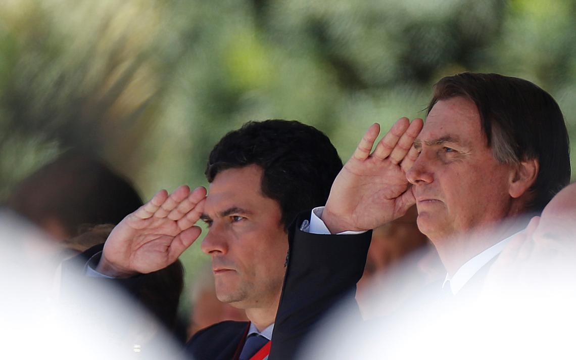 Sergio Moro e Jair Bolsonaro prestam continência durante cerimônia em Brasília