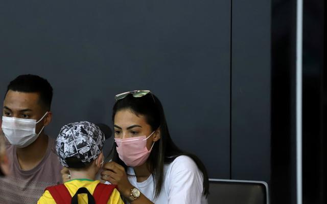 Mulher, de máscara no rosto, ajeita posicionamento de máscara no rosto de menino pequeno. Ele está de costas para a câmera.