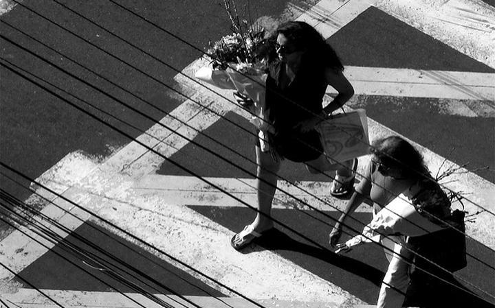 Foto de cima de duas mulheres atravessando a rua segurando buquês de flores. A foto está em preto e branco.