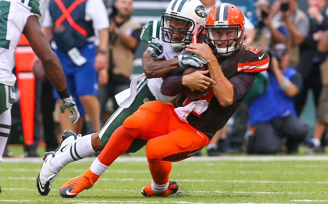 Em disputa pela bola em jogo da NFL, o capacete de dois jogadores de times opostos se chocam.
