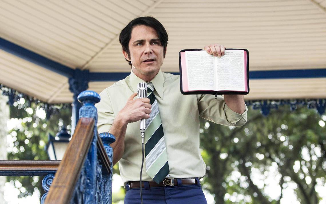 Homem segura Bíblia na mão enquanto discursa