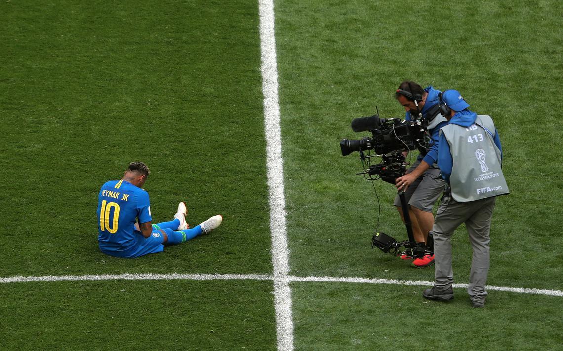 Neymar chora no gramado após vitória sobre a Costa Rica na Copa do Mundo, acompanhado de perto pela equipe de transmissão da Fifa