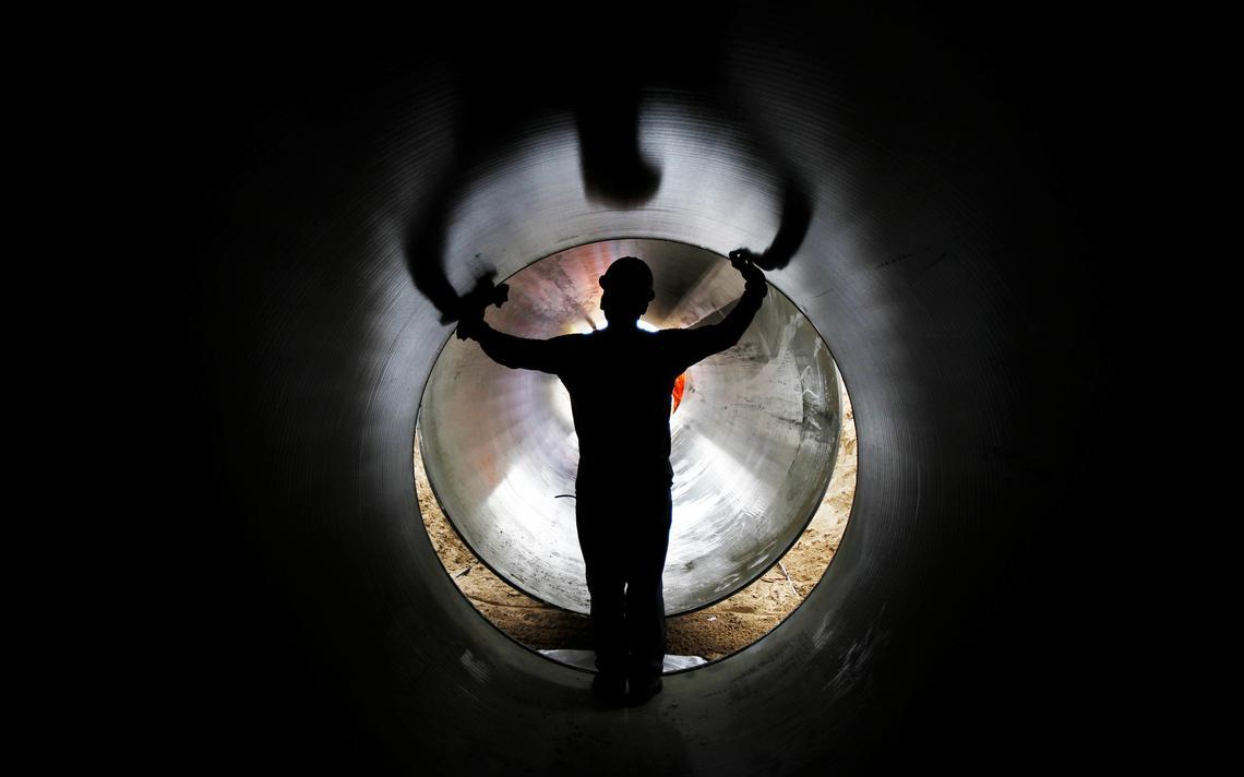 Operário em duto de estrutura de irrigação da Odebrecht