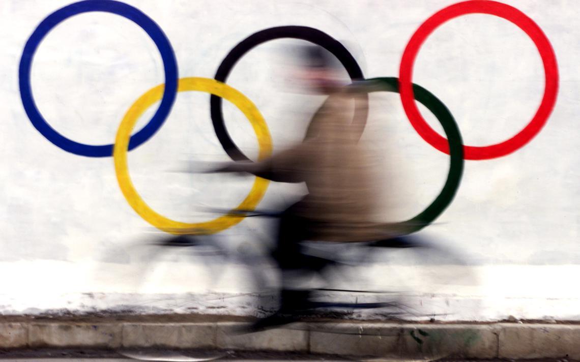 Chinês na frente dos aneis olímpicos em Pequim