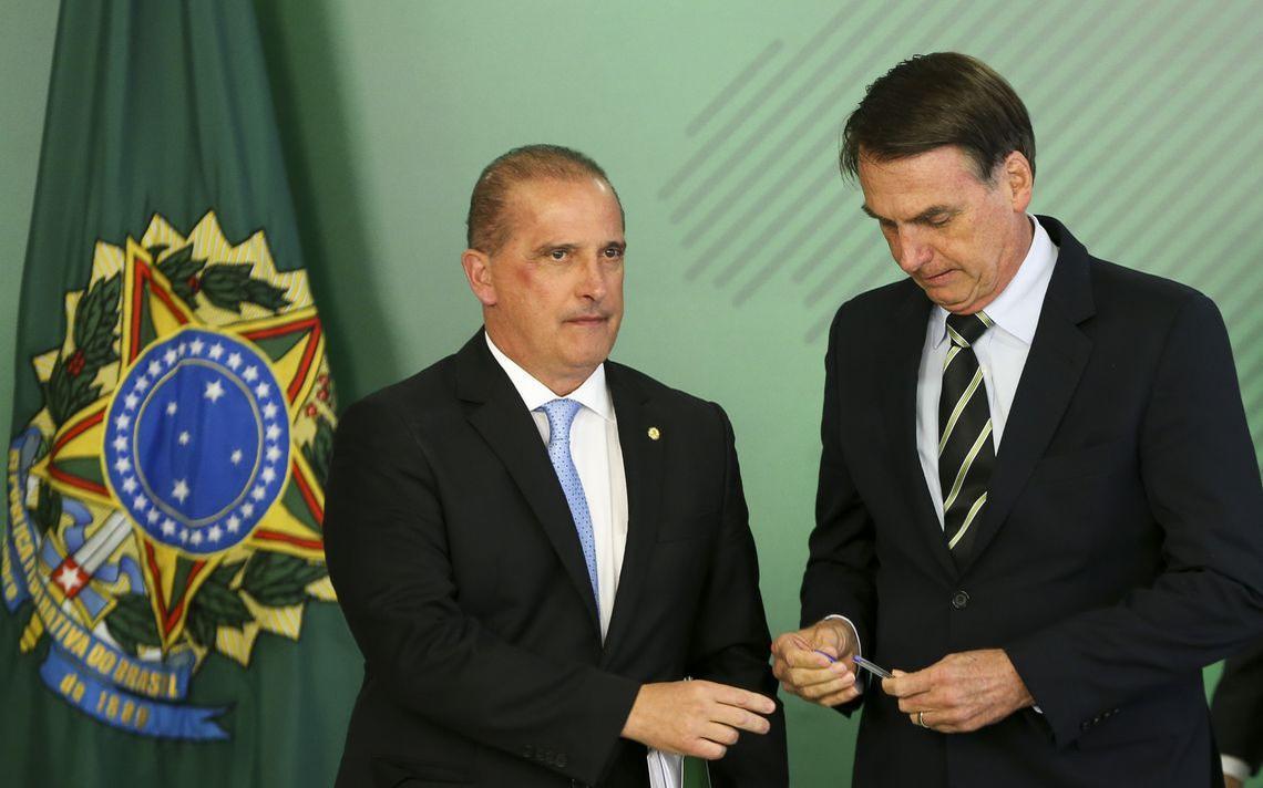 Bolsonaro maneja uma caneta e olha para o objeto. Ao lado dele, o ministro Onyx estende a mão na direção da caneta. Atrás há bandeira com o brasão da República.
