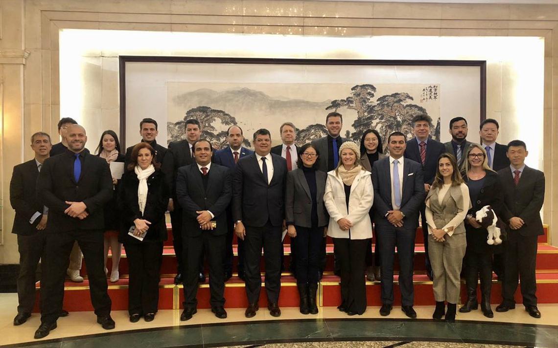 Políticos posam para foto. Estão em pé, em duas filas. Atrás, um grande quadro chinês.