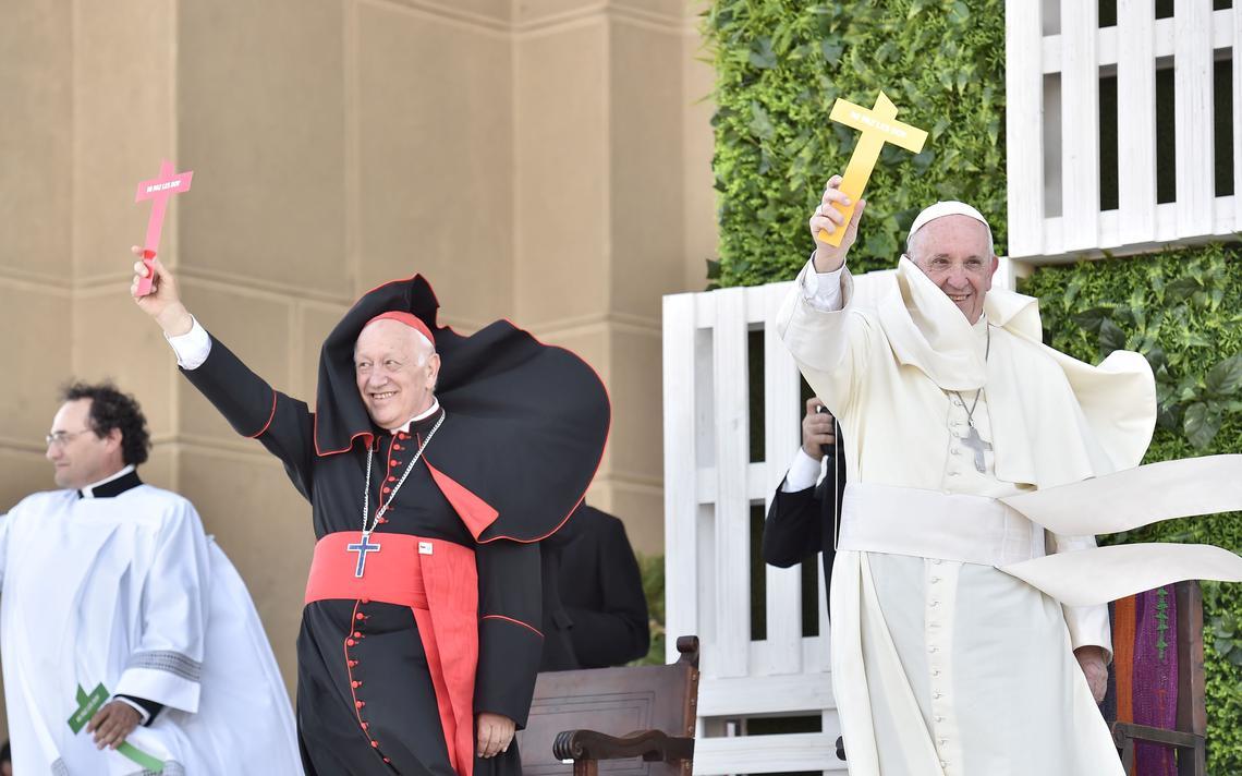 Sorrindo, papa segura e ergue uma cruz em altar. Ao lado dele, um cardeal faz o mesmo. O ambiente é aberto.